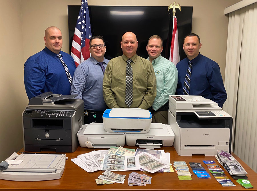 During a search of the motel room, detectives located five printers, a laptop computer, multiple cellular devices, a bag of computer cables, and several miscellaneous items, all commonly used to replicate bills of U.S. currency.