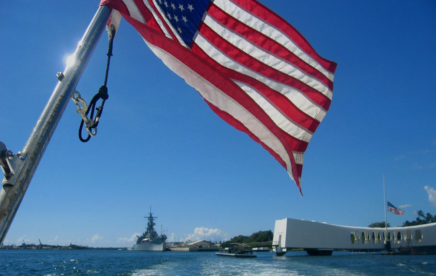 United States of America flag flying above the USS Arizona Memorial in Pearl Harbor on the island of Oahu. Photo credit ShutterStock.com, licensed.