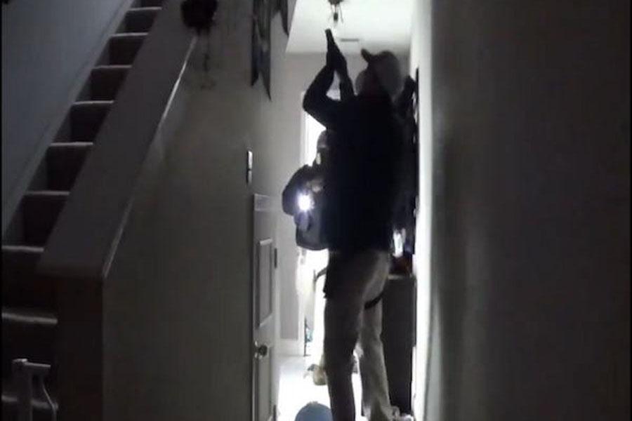 A police officer wields a gun and calls for Rebekah Jones' husband to come downstairs. Photo credit: Rebekah Jones/Twitter.