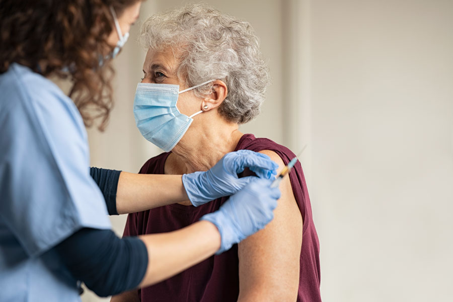 A senior receives a Pfizer-BioNtech Covid-19 vaccine from a healthcare worker at Coral Gables in Miami, Florida.
