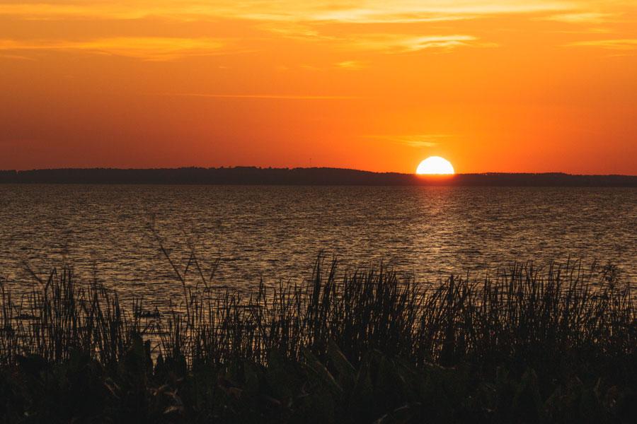 Sunset over distant hills on Lake Apopka in Apopka, Florida. Photo credit ShutterStock.com, licensed.