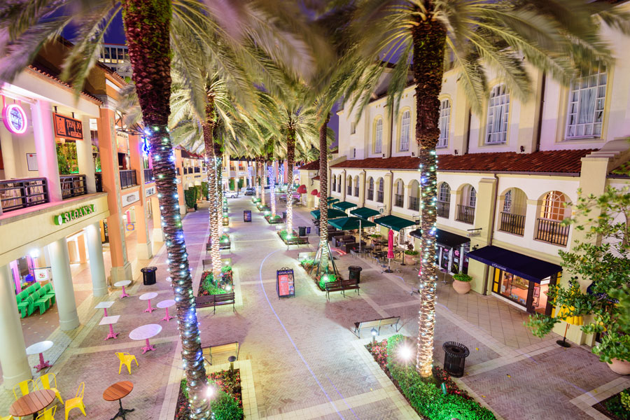 Palm trees line the mixed-use development CityPlace (now Rosemary Square) at night. Shops and restaurants fill the streets between Rosemary Avenue and Clematis Street, West Palm Beach, Florida - April 3, 2016. Editorial credit: Sean Pavone / Shutterstock.com, licensed.
