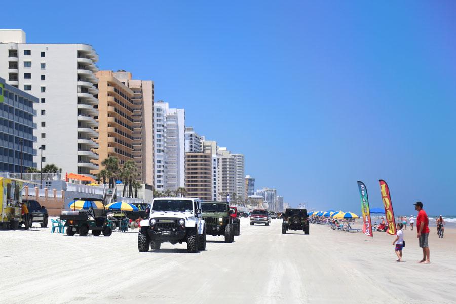 Multi-colored jeep wranglers ride on Daytona Beach. Daytona Beach, Florida - May 1 2019. Editorial credit: RudenkoStudio / Shutterstock.com, licensed.