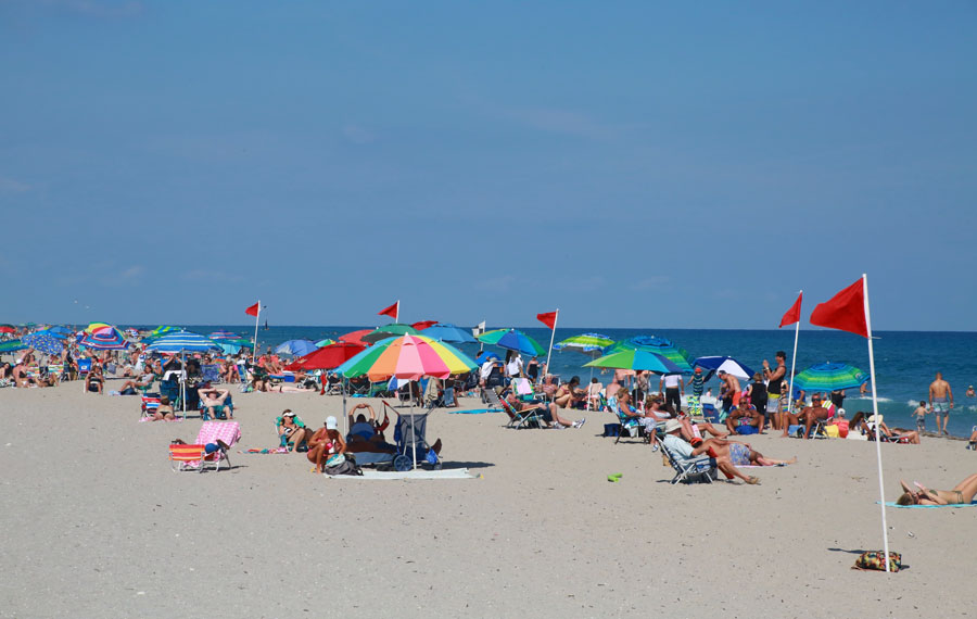 Sunbathers under colorful umbrellas line up on the beach in a clear sunny afternoon. Editorial credit: Mike Kuhlman / Shutterstock.com, licensed.