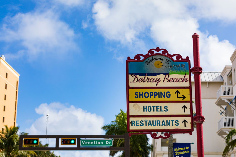 Delray Beach welcome sign on the popular Atlantic Avenue offers directions and arrows.