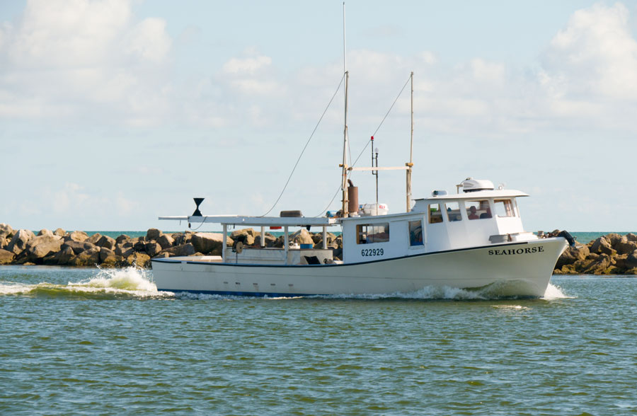 A shrimp fishing boat charter sails in the waters off nearby St George Island coast in Florida. Editorial credit: Leigh Trail, Shutterstock.com, licensed.