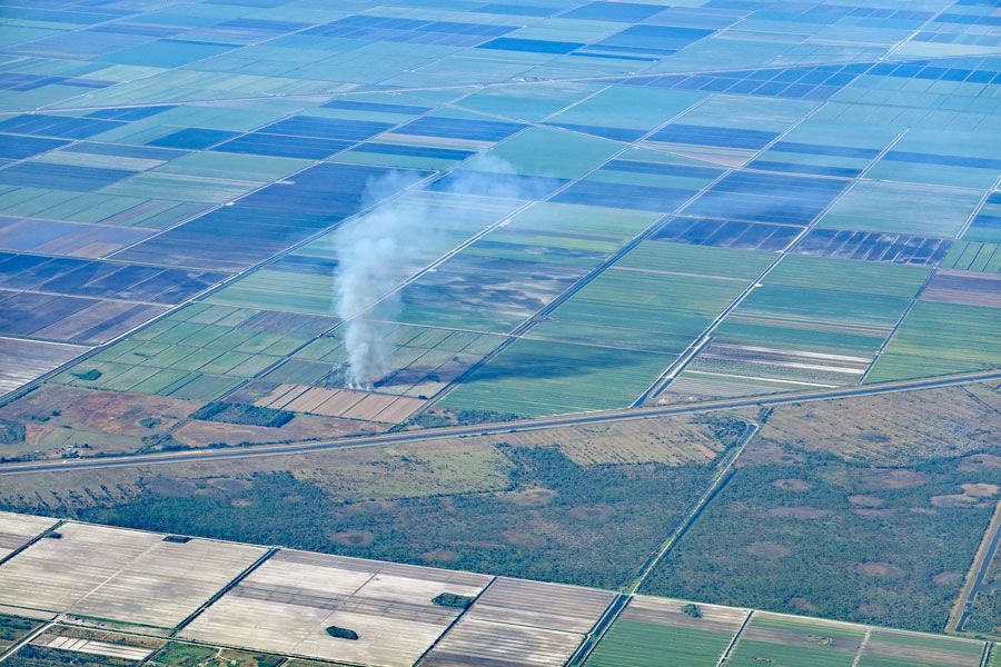 Aerial view of the sugar cane fields, burning, in South Florida, near Lake Okeechobee, Belle Glade, South Bay and Pahokee. It causes air pollution. Photo credit ShutterStock.com, licensed.