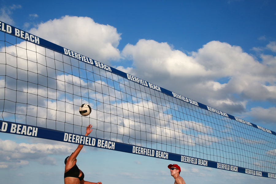 Young women play volleyball near the labelled net in a bright sunny afternoon with scattered clouds. Deerfield Beach, Florida, January 13 2018.