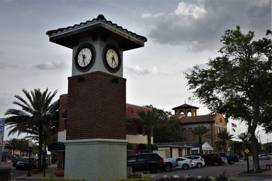 Clock tower in the city park of Auburndale, Florida, with the Flatiron Building and City Hall visible in the background.
