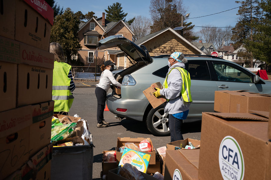 Volunteers load food packages into clients' cars in Englewood, New Jersey.