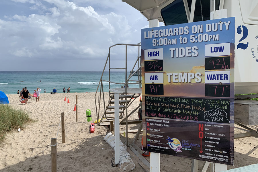 A sign showing lifeguards on duty from 9AM to 5PM in Lake Worth Beach. Water temperatures were 77 degrees  on this warm  January day in 2021.