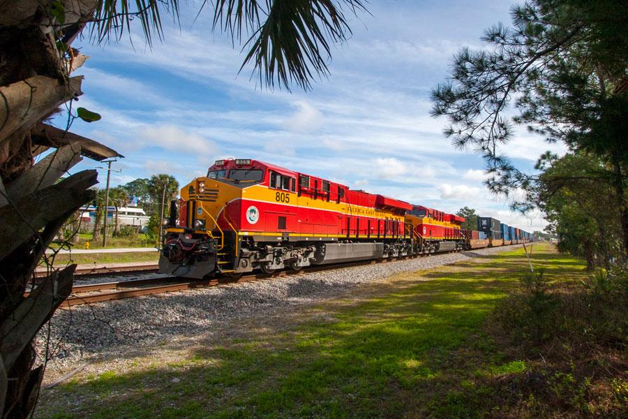 Florida East Coast Railway train 210 framed by palms. Bunnell, Florida, January 12 2015. Editorial credit: Drew Halverson / Shutterstock.com, licensed.