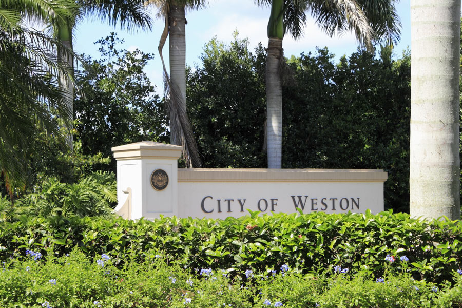 Entrance sign to the city of Weston, Florida, located in western Broward County, with beautiful flowers in front and tropical foliage behind on a sunny day