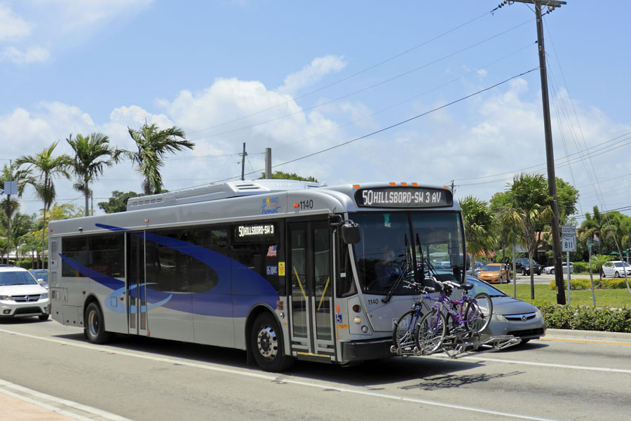 Blue and gray silver public transportation with two bicycles securely stored on the front of the bus as it travels through the sunny day city on Wilton Drive. Wilton Manors, Florida
