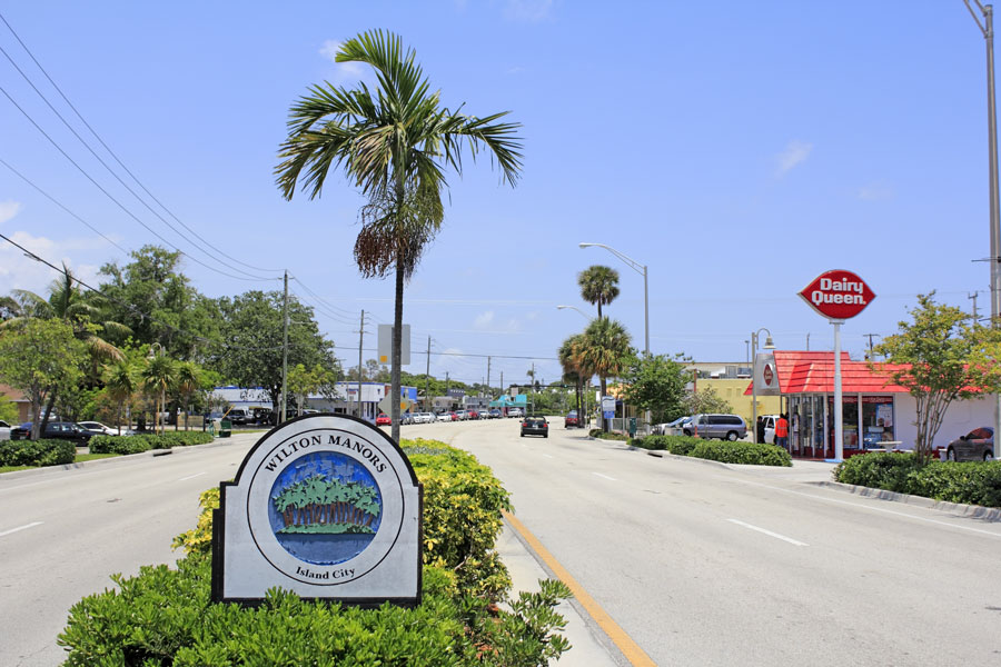 Sign that says Wilton Manors and Island City with palm trees on an island graphic in the median of Wilton Drive in this urban city of 12,630 in 2019. Wilton Manors, Florida, May 11, 2013.