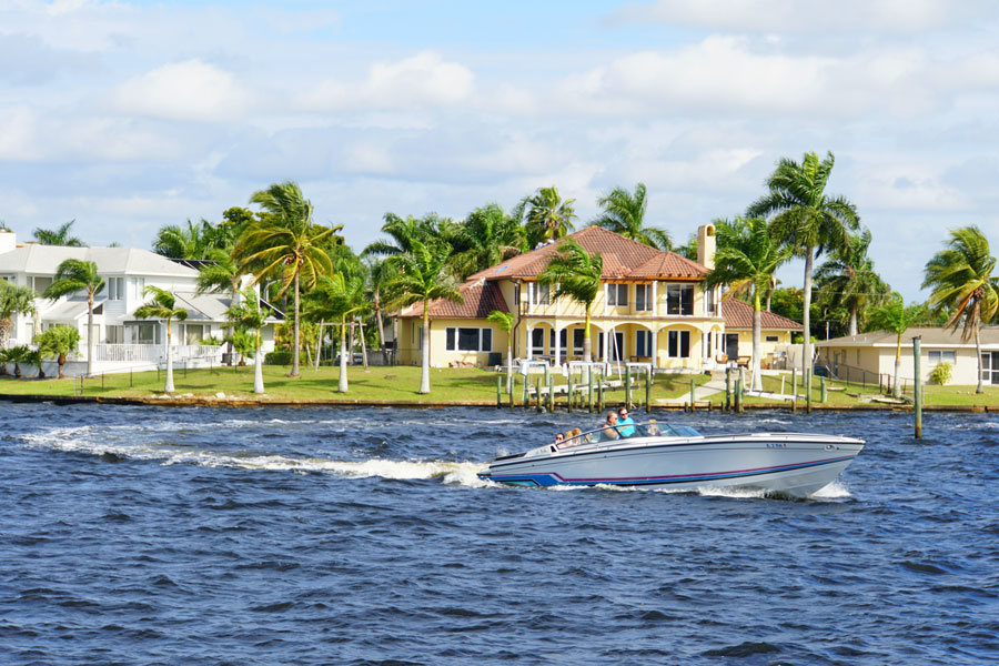 The view of a boat and waterfront home by the bay in Cape Coral, Florida on December 3, 2018. Editorial credit: Khairil Azhar Junos / Shutterstock.com, licensed.