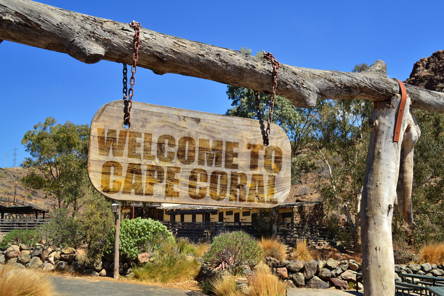 """An old wood signboard with text """"Welcome to Cape Coral"""" hanging on a branch. Photo credit ShutterStock.com, licensed."""