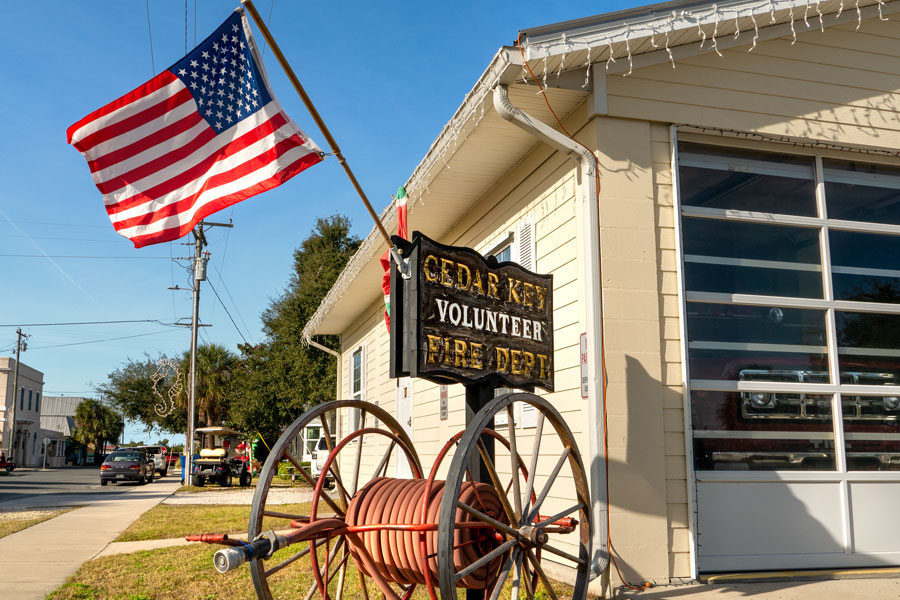 Volunteer Fire Department with American flag and firetruck parked in garage in downtown Cedar Key, Florida.