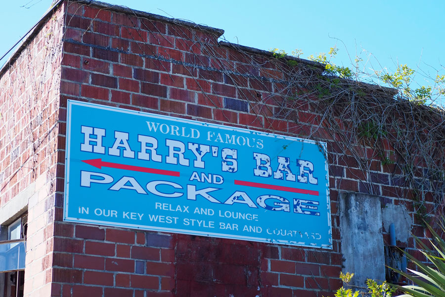 Sign and old brick wall for Harry's Bar in historic Carrabelle, Florida on March 23, 2019. Editorial credit: Ken Weaver / Shutterstock.com, licensed.