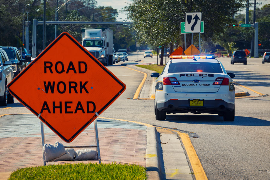 Police car staying on the road with lights for traffic control in road work zone. Coconut Creek, Florida, on February 05, 2021. Editorial credit: YES Market Media / Shutterstock.com, licensed.