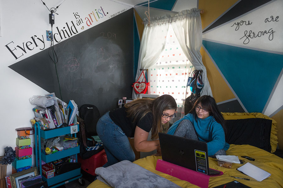 """Rocio Alvarado looks over daughter Rhianna's online class schedule, which includes animation drawing, speech therapy and acting class. """"Caring for her dad came naturally to her,"""" Rocio said. She's overprotective and will stop what she's doing to check on him."""