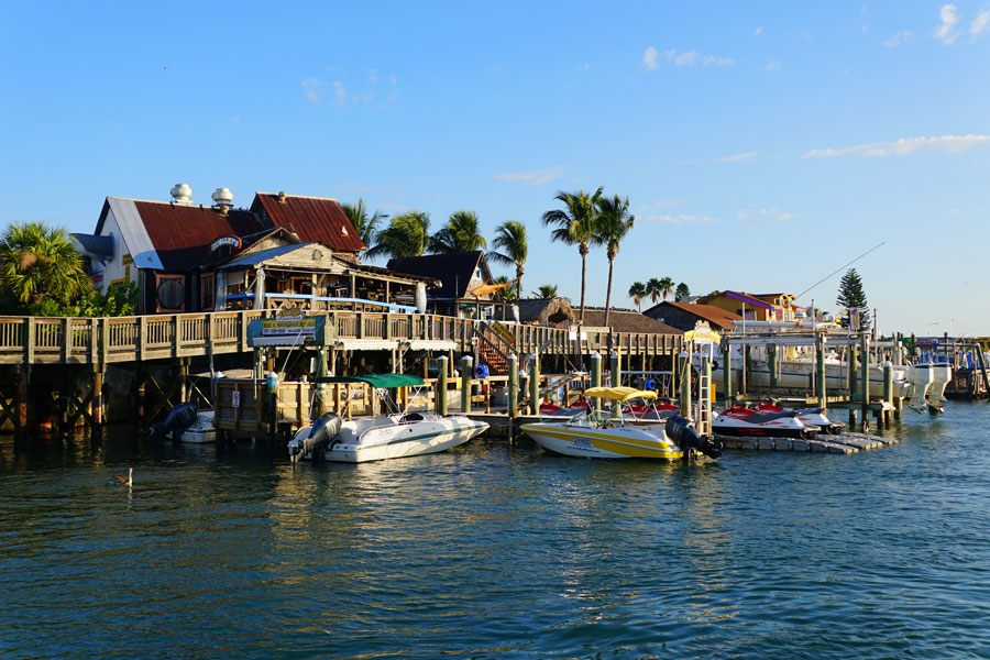 The restaurants and boats on the dock by John's Pass Boardwalk and the canal in Madeira Beach, Florida on September 29, 2019.