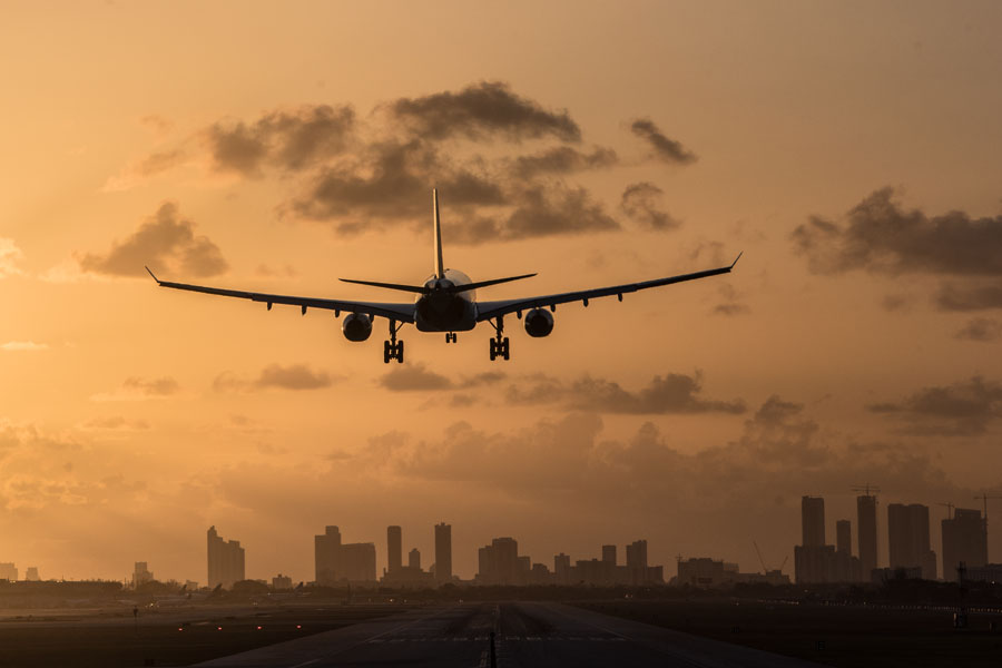 Airplane landing at Miami International Airport at sunrise with Miami Downtown skyline in the background.