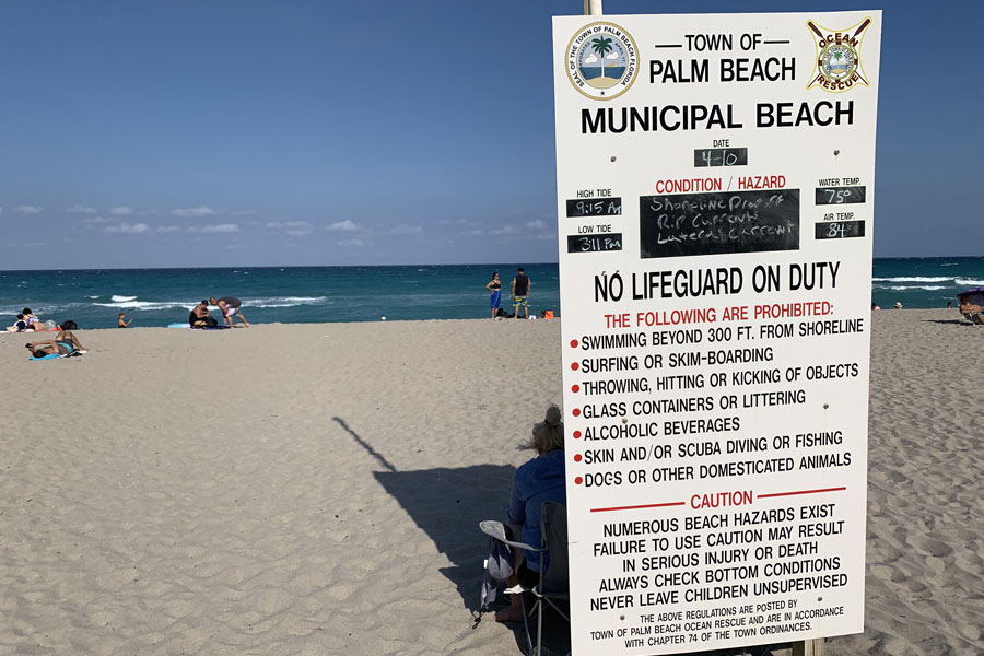 A town of Palm Beach Municipal Beach sign showing 75 degree waters and an air temperature of 84.