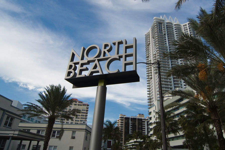 Residential buildings and a North Beach welcome sign in North Miami Beach, Florida.