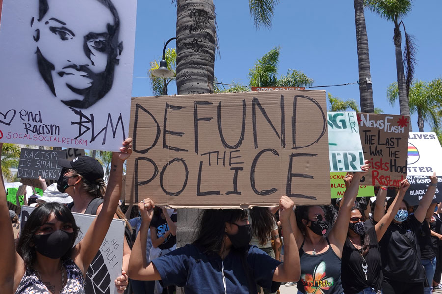 People hold signs during peaceful Black Lives Matter protest march, one of many in San Diego County. One sign reads Defund Police.