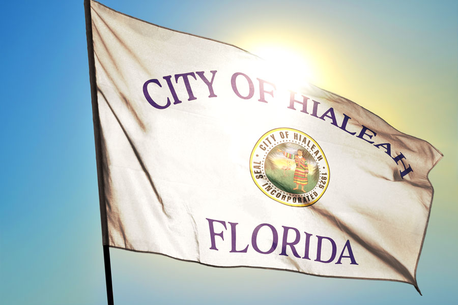 A City of Hialeah Florida flag waving on the wind in front of the sun. Photo credit ShutterStock.com, licensed.
