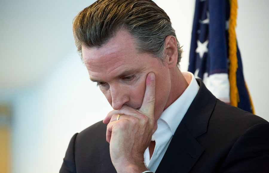 California State Governor Gavin Newsom holds his head in though before a meeting.