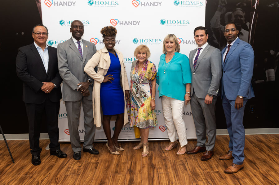 Paul Minoff, H.O.M.E.S. Inc. Board Member; Linda Taylor, H.O.M.E.S. Inc. CEO, Kirk Brown, HANDY CEO; and Dan Young, HANDY Board Chair Signing the Strategic Alliance. . Photo Courtesy of Downtown Photo.