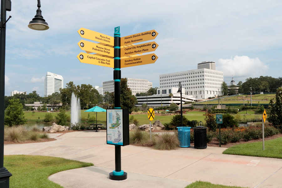 Four-way directional sign each point to 12 local locations. Sunny Cascades park near downtown Tallahassee, FL, July 15, 2018.