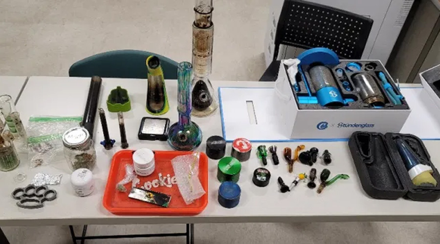 Deputies located 2.2 grams of mushrooms, one stundenglass vaporizer, eight bongs, nine smoking bowls, five grinders, two acid strips that were wrapped in a piece of tin foil, marijuana totaling 13.2 grams, 1 pair of brass knuckles, 1 black digital scale, 1 green rubber ashtray, rolling papers and 2 clear plastic bags.