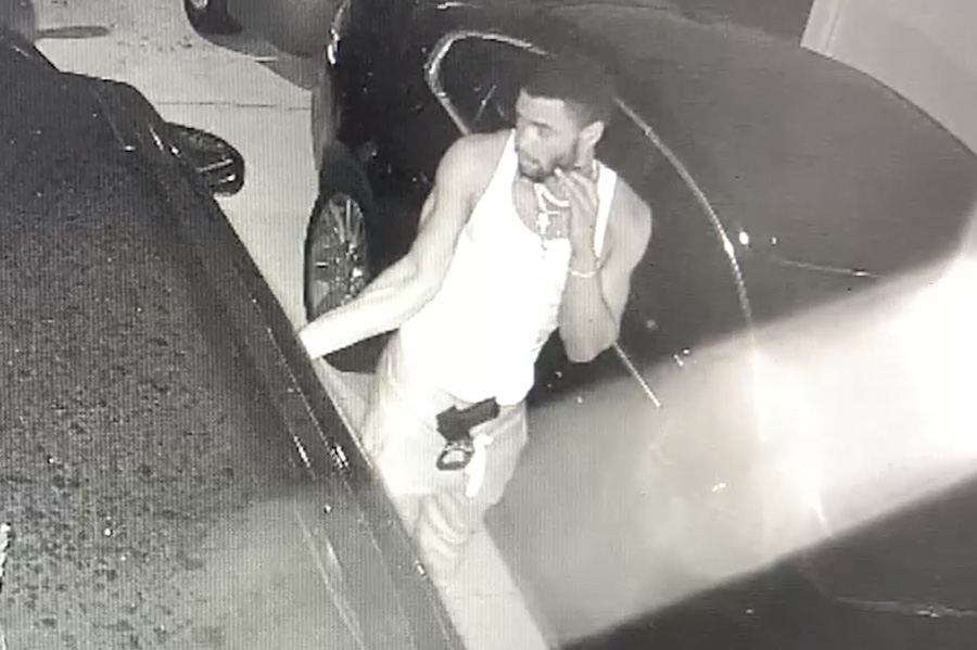 The video shows a young male wearing a white tank top, light colored pants and several necklaces around his neck with a short dark beard, short dark hair and a black handgun in the front of his waistband.