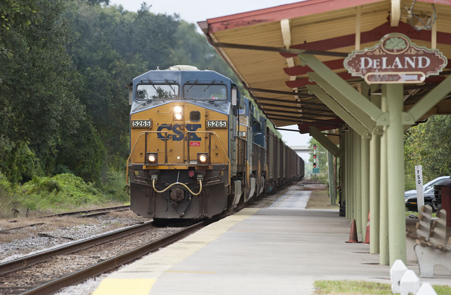 A CSX freight train hauling boxcars passing DeLand station in DeLand Florida in November 2013