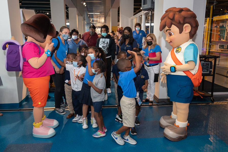 Learners from Jack & Jill Children's Center meeting Dora and Diego while entering the exhibit.