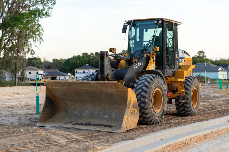 A road construction front loader parked in the Arbor Greens subdivision off Newberry Road where new housing construction will begin once the road has been completed.