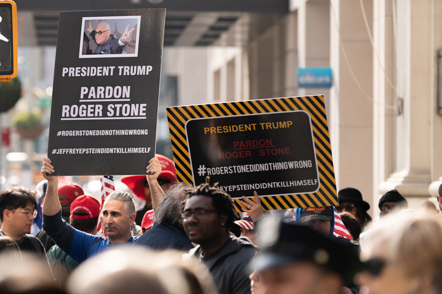 Pardon Roger Stone signs being held up during a Veterans Day Parade in Manhattan